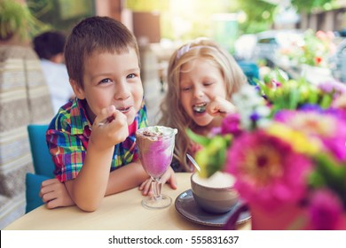 Little boy with a girl eating ice cream at an outdoor cafe in outdoor cafe