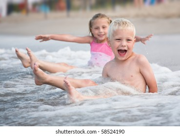 Little boy and girl enjoy waves of the sea