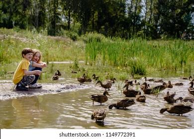 Little boy and girl feeding ducks on abandoned lake.