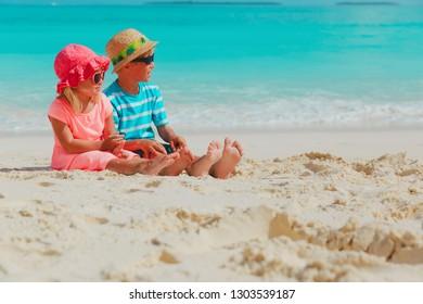 little boy and girl having fun on beach