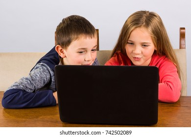 Little boy and girl having fun on a laptop computer