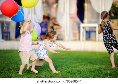 Little boy and girl having fun during celebrating birthday party. Happy child with with colorful balloons. Preschoolers or toddlers birthday party in outdoor cafe