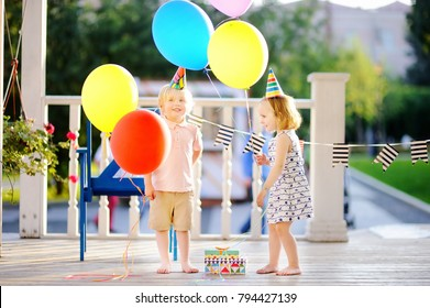 Little boy and girl having fun and celebrate birthday party with colorful balloons. Happy child with festive gifts. Preschoolers or toddlers birthday party in summer park