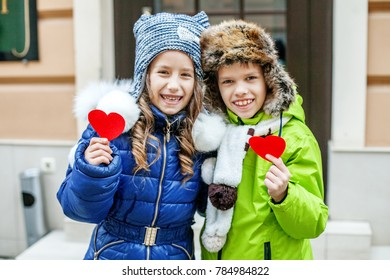 Little boy and girl holding red heart. Two children. The concept of friendship, love, Valentine's Day.