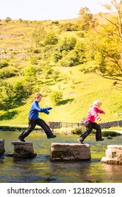 A little boy and girl hoping, jumping over stepping stones across a river, stream in the Dovedale, Peak District National Park, famous public walking trails, outdoor parks, ADHD, Autism, Aspergers