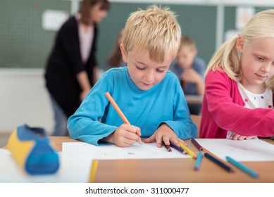 Little boy and girl in kindergarten class sitting at a desk writing and drawing on sheets of paper as the teacher works with another pupil in the background