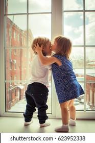 Little boy and girl kissing on big window