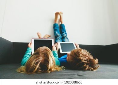 little boy and girl looking at touch pad at home