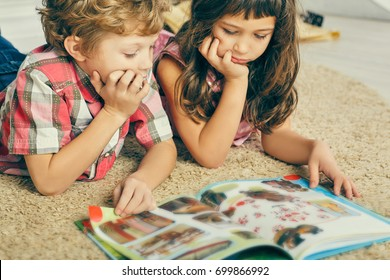 Little boy and girl lying on the floor and reading an illustrated book.
