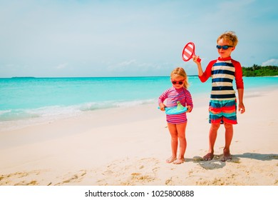 little boy and girl play beach tennis on vacation