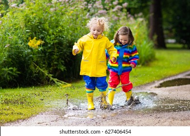Little boy and girl play in rainy summer park. Children with colorful rainbow jacket and waterproof boots jump in puddle and mud in the rain. Kids walk in autumn shower. Outdoor fun by any weather