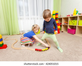 Little boy and girl play with toy railway in kindergarten