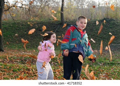 little boy and girl playing with autumn leaves in the park