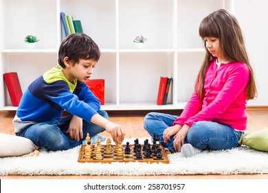 Little boy and little girl are playing chess at home.Children playing chess