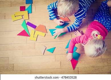 little boy and girl playing with geometric shapes