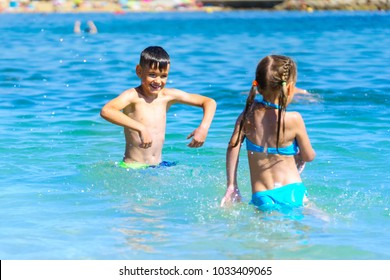 Little boy and girl playing splashing sea water on beach holiday
