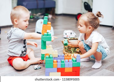 little boy and girl playing toys at home communication two years old
