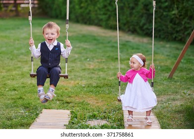 Little boy and girl ride in the park on a swing.