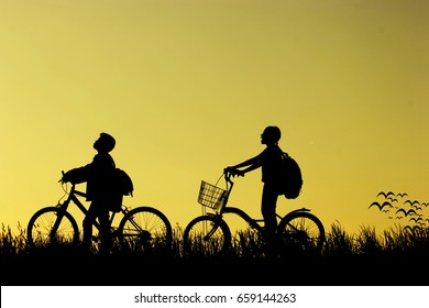 little boy and girl riding bikes at sunset, active kids sport, Asian kid,Silhouette a kid at the sunset, Happy time.