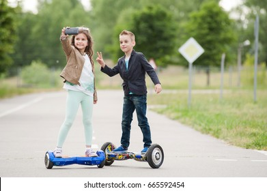 little boy and girl riding on the hoverboard in the park