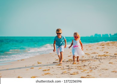 little boy and girl running at beach vacation