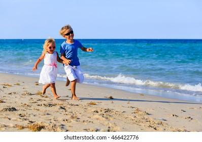 little boy and girl running at beach