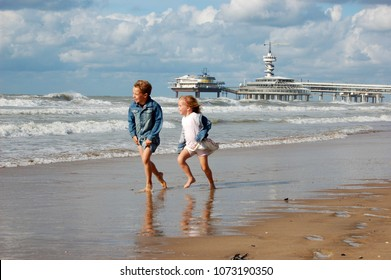 Little boy and girl running in denim clothing in the surf of the sea, with a pedestrian promenade in the background. Scheveningen, The Netherlands, Europe.