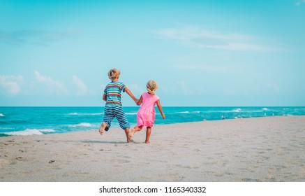 little boy and girl running on beach