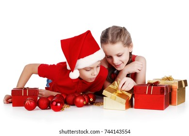 Little boy and girl with Santa hat holding toys for the New year. Christmas gifts. Isolated on white