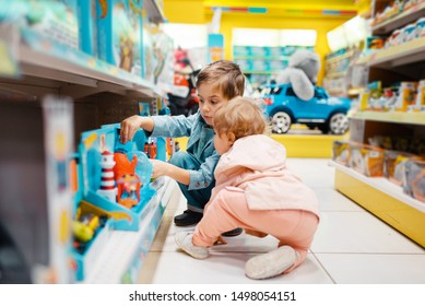 Little boy and girl at the shelf in kids store