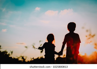 little boy and girl silhouettes holding hands at sunset