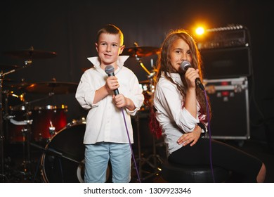 little boy and girl singing in recording studio