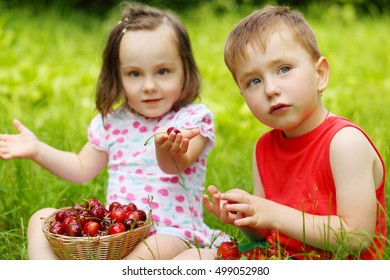 Little boy and girl sit on grass and eat strawberries, cherry in park, focus on boy