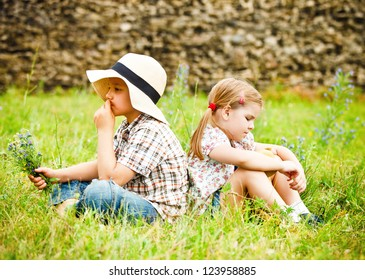 Little boy and little girl siting back to back near the country house