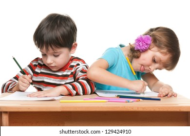 Little boy and little girl are sitting at the desk and write