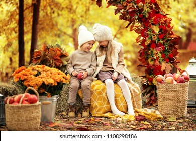 little boy and girl are sitting on haystacks in the autumn landscape