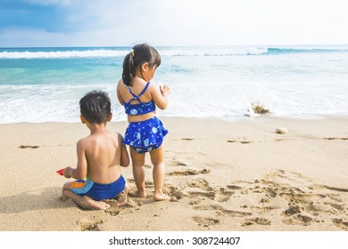 Little boy and girl sitting on the sand