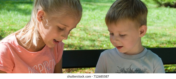 A little boy and girl are sitting on the bench and talking.