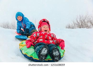 little boy and girl sliding in winter snow