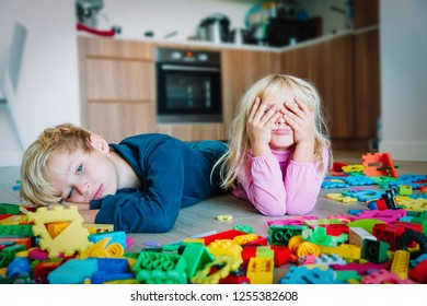 little boy and girl tired stressed exhausted with toys scattered indoors