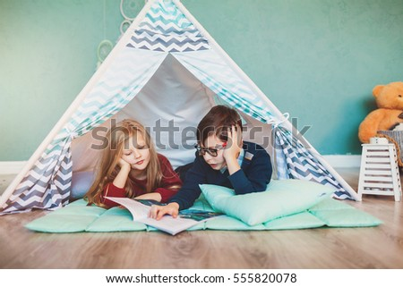 Little boy and girl together reading interesting book indoors in kids wigwam