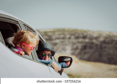 little boy and girl travel by car in mountains