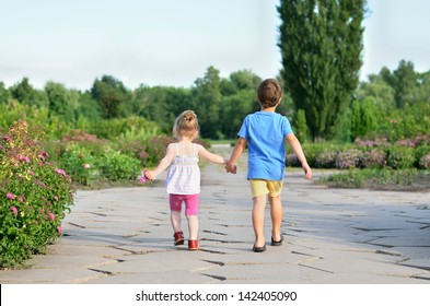 Little boy and girl walking hand in hand in the park