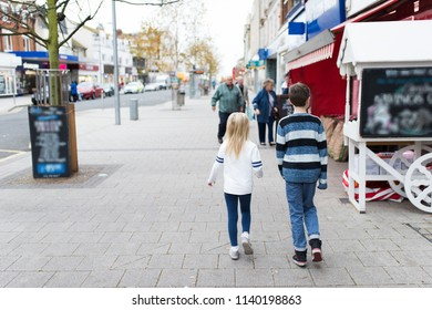 A little boy and girl walking in the high street having fun on holiday, Clacton on Sea, Essex, England