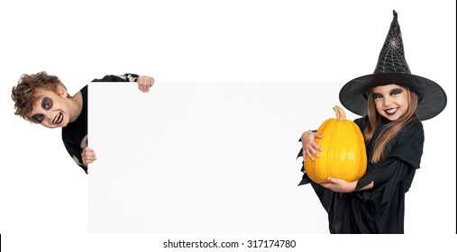 Little boy and girl wearing Halloween costume with pumpkin and blank board on white background