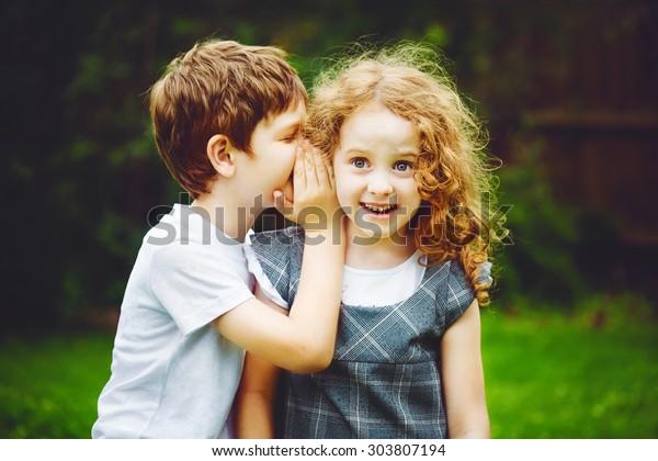 Kleiner Junge und Mädchen flüstern.