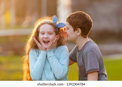 Little boy and girl whispers in spring outdoors. New rumors. Happy childhood concept.