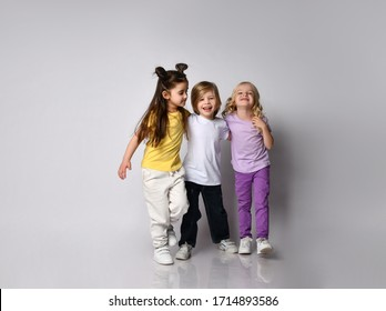 Little boy and girls dressed in colorful casual clothes. They are smiling and hugging each other, posing isolated on white studio background. Childhood, fashion, advertising. Full length, copy space