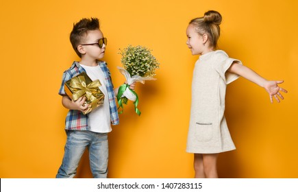 A little boy gives a bouquet of daisies to his girlfriend a girl. girl is happy to present and spread her arms wide to hug him. Concept of friendship, quarrel, date