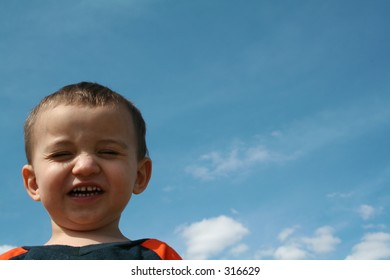 Little boy gives a cheesy grin against a blue sky.